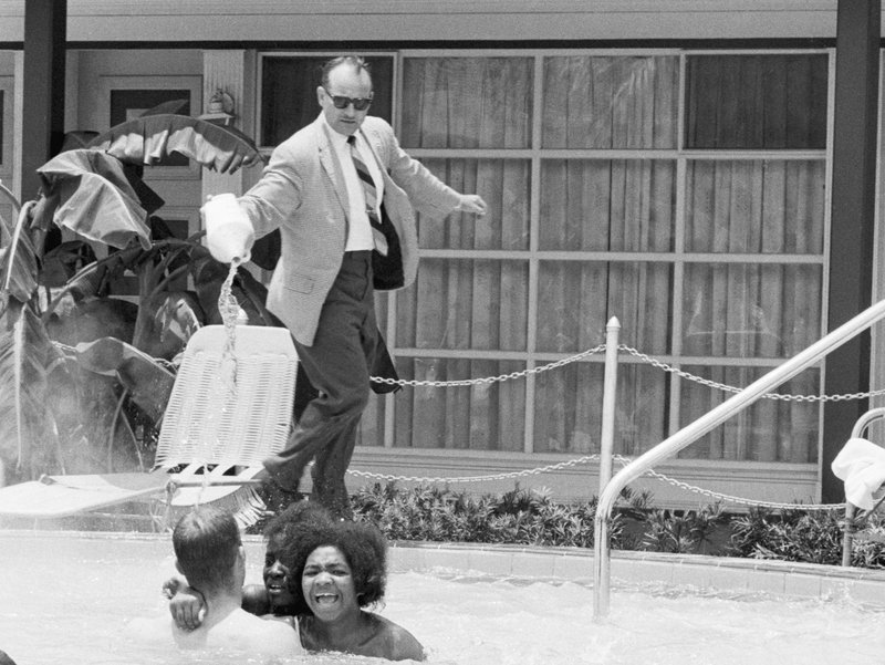 Hotel-owner-pouring-acid-in-the-pool-while-black-people-swim-in-it-ca-1964