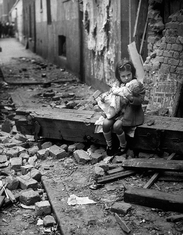 Little-girl-with-her-doll-sitting-in-the-ruins-of-her-bombed-home-London-1940